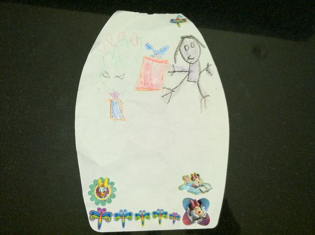 Audrey placing a gift under the Christmas tree, in crayon and with stickers